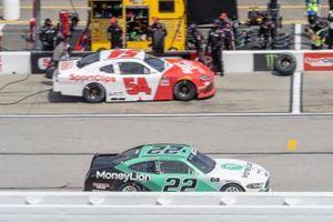 Austin Cindric, Team Penske, Ford Mustang MoneyLion passes Denny Hamlin, Joe Gibbs Racing, Toyota Supra SportClips in the pits