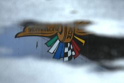 The Indianapolis Motor Speedway logo is reflected in a puddle of rain water