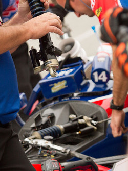 Crew members working on the suspension of Takuma Sato, A.J. Foyt Enterprises Honda's car