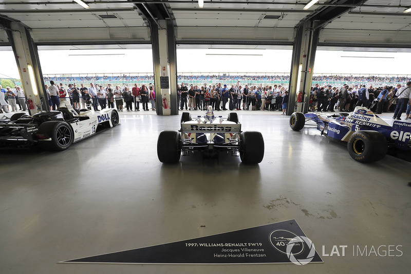 Fans view a garage containing the 1999 BMW Le Mans winner and classic Williams F1 cars