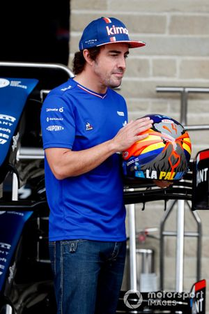Fernando Alonso, Alpine F1, poses with a crash helmet that depicts the volcano in La Palma