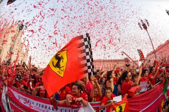 A Ferrari flag waves as confetti is launched over the crowd