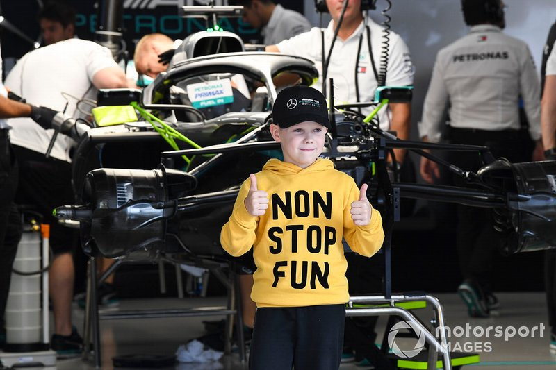 A young fan poses in the Lewis Hamilton, Mercedes AMG F1 garage