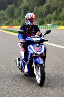 Pierre Gasly, Toro Rosso, rides the track on a scooter
