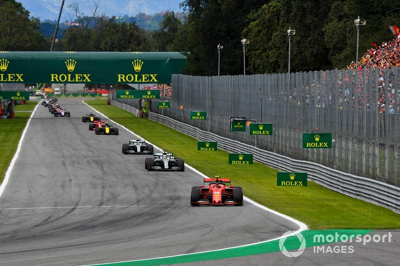 Charles Leclerc, Ferrari SF90, leads Lewis Hamilton, Mercedes W10, and Valtteri Bottas, Mercedes W10 at the Parabolica on the opening lap