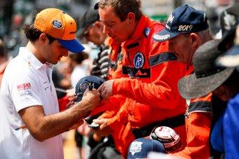 Carlos Sainz Jr., McLaren signs a autograph for a marshal
