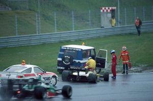 Patrick Tambay accanto alla sua Renault RE50 danneggiata durante le prove, mentrei marshal recuperano la monoposto e Riccardo Patrese, Alfa Romeo 184T, transita