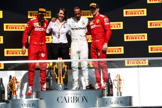 Sebastian Vettel, Ferrari, 2nd position, the Mercedes Constructors trophy recipient, Lewis Hamilton, Mercedes AMG F1, 1st position, and Charles Leclerc, Ferrari, 3rd position, on the podium