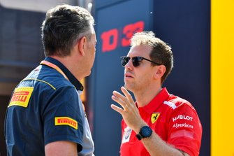 Sebastian Vettel, Ferrari an Mario Isola, Racing Manager, Pirelli Motorsport talk in the paddock