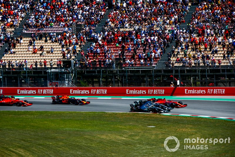 Lewis Hamilton, Mercedes AMG F1 W10, Valtteri Bottas, Mercedes AMG W10, and Sebastian Vettel, Ferrari SF90, race side by side ahead of Max Verstappen, Red Bull Racing RB15, and Charles Leclerc, Ferrari SF90, in the first corner at the start