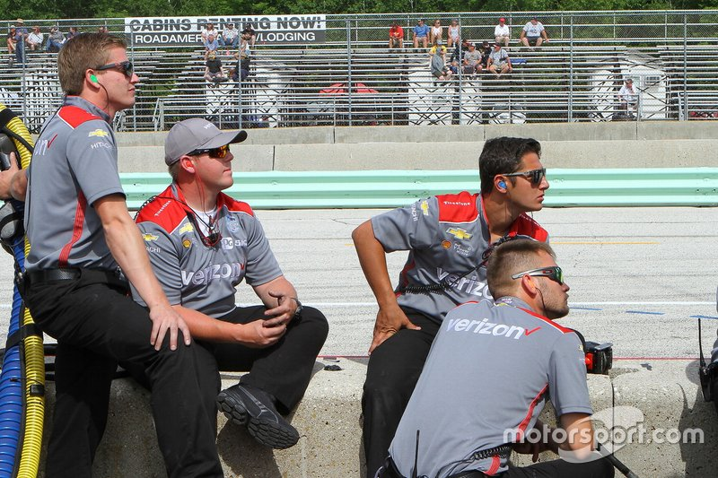 Penske crew members watch the timing screen during qualifying