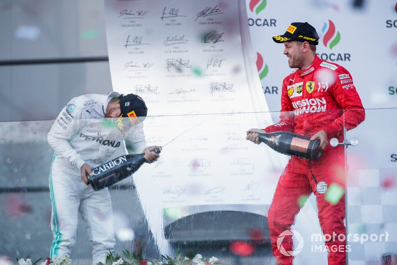 Valtteri Bottas, Mercedes AMG F1, 1st position, and Sebastian Vettel, Ferrari, 3rd position, celebrate on the podium with Champagne
