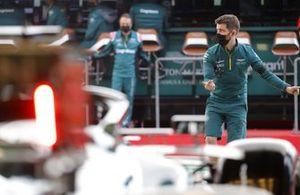 Un mécanicien dirige Lance Stroll, Aston Martin AMR21, hors de son garage