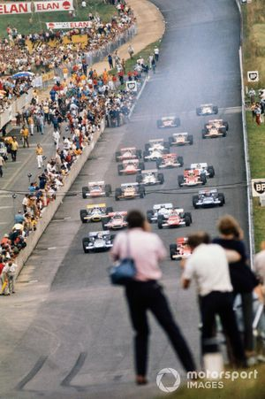 Jochen Rindt, Lotus 72C Ford, leads Jackie Stewart, March 701 Ford, and the rest of the field at the start, as a photographer steps onto the track for a better angle