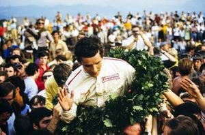 Fans gather around race winner Jacky Ickx at the podium ceremony