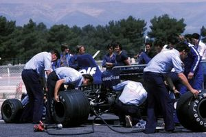 The Tyrrell mechanics make a tyre change on the 007 whilst Ken Tyrrell, Tyrrell Team Owner talks to the driver