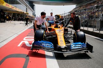 McLaren mechanics push the car of Carlos Sainz Jr., McLaren MCL34, in the pit lane