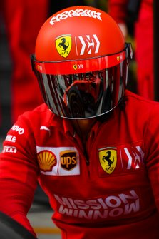 A Ferrari team member at work. His visor reflects a practice pit stop