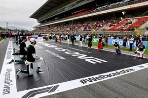 The drivers stand and kneel in support of the End Racism campaign on the grid, prior to the start