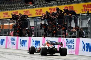 Sergio Perez, Red Bull Racing RB16B, is cheered over the line by his team