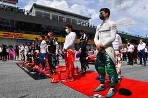 Lance Stroll, Aston Martin, Charles Leclerc, Ferrari, Valtteri Bottas, Mercedes, Lando Norris, McLaren, and the other drivers stand for the national anthem