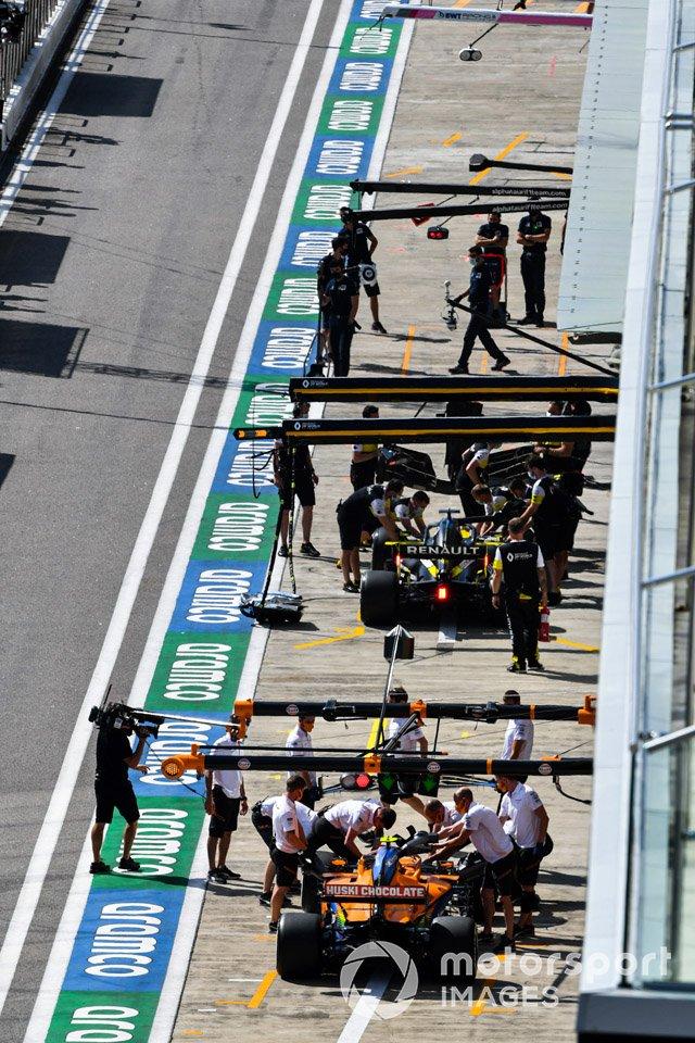 Daniel Ricciardo, Renault F1 Team R.S.20, y Carlos Sainz Jr., McLaren MCL35, in the pit lane