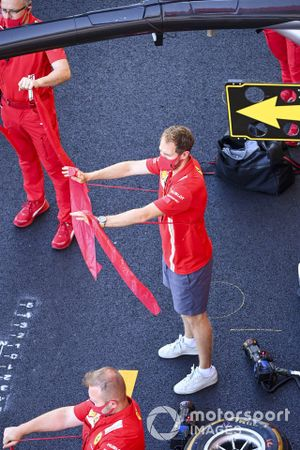 Sebastian Vettel, Ferrari warms up with his team in the pit lane