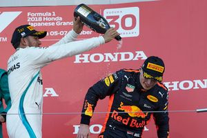 Lewis Hamilton, Mercedes AMG F1, celebrates his win on the podium spraying champagne on Max Verstappen, Red Bull Racing