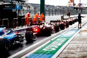 Carlos Sainz Jr., Ferrari SF21, Antonio Giovinazzi, Alfa Romeo Racing C41, et Fernando Alonso, Alpine A521, font la queue dans la voie des stands