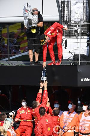Charles Leclerc, Ferrari, 2nd position, passes his Champagne bottle to his team from the podium