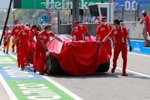 Ferrari mechanics with the covered car of Carlos Sainz Jr., Ferrari SF21