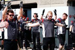 Haas F1 Team team members loosen up by taking exercises