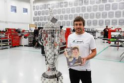 Fernando Alonso with the Borg-Warner trophy and the 1981 Indy 500 yearbook