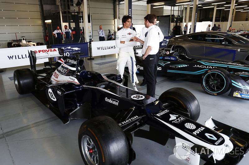 Lance Stroll, Williams, stands between a 2012 Williams FW34 Renault Sport F1 Team and Jaguar Formula E car