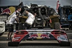 Des mécaniciens Peugeot Sport travaillent sur une 2008 DKR