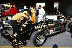 Nigel Mansell, habla con su esposa Roseanne Mansell, mientras los mecánicos trabajan en su Lotus 87 en el área del pit