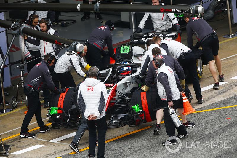 Romain Grosjean, Haas F1 Team VF-18, is attended to by mechanics in the pit lane