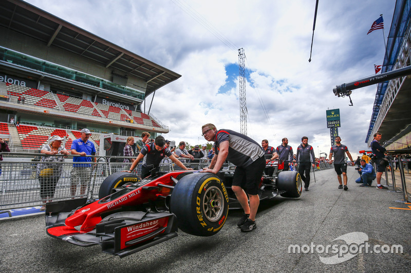 Haas F1 Team team members push the car of Kevin Magnussen, Haas F1 Team VF-17, in the pit lane