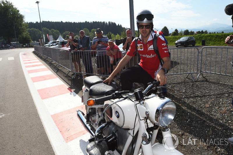Sebastian Vettel, Ferrari llega al circuito en su moto vintage BMW.