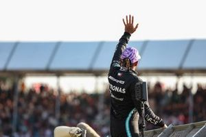 Pole man Lewis Hamilton, Mercedes, climbs a catch fence to wave to fans