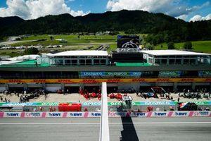 Carlos Sainz Jr., Ferrari SF21, and Charles Leclerc, Ferrari SF21, are returned to the garage