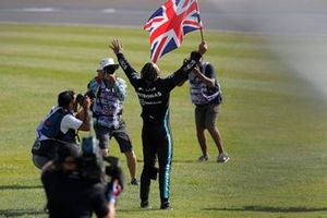 Lewis Hamilton, Mercedes, 1st position, celebrates on the infield with a Union flag after the race
