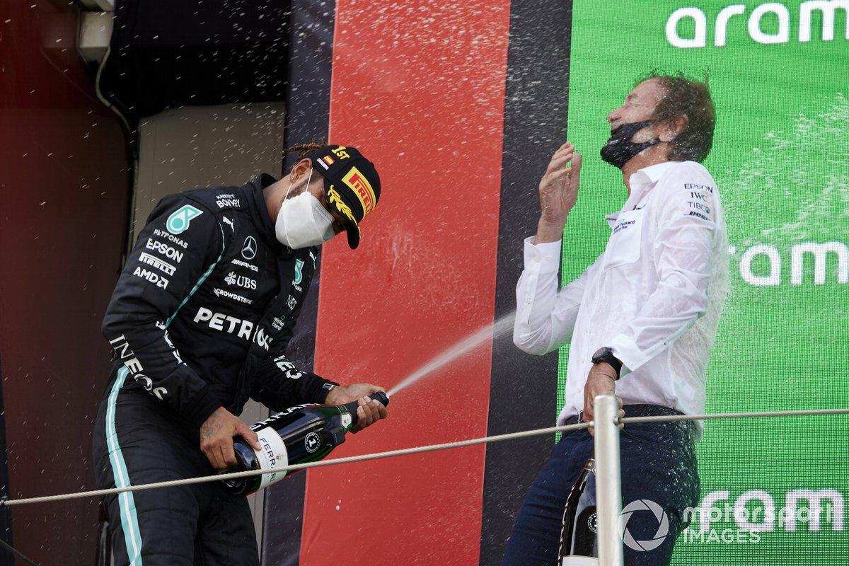 Lewis Hamilton, Mercedes, primera posición, derrama champán a su compañero de equipo en el podio