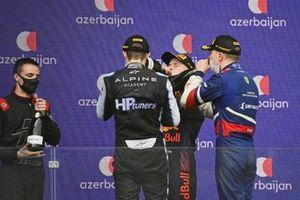 The Hitech Grand Prix representative, Oscar Piastri, Prema Racing, 2nd position, Juri Vips, Hitech Grand Prix, 1st position, and Robert Shwartzman, Prema Racing, 3rd position, enjoy champagne on the podium