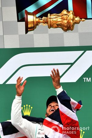 Lewis Hamilton, Mercedes AMG F1, 1st position, tosses his trophy in the air in celebration on the podium