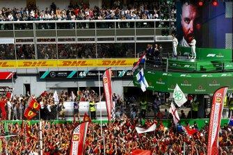 The crowd celebrates a win for Ferrari at home, beneath the podium ceremony