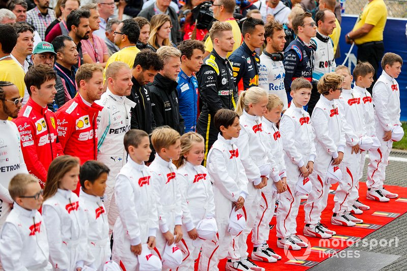 The drivers join the Grid Kid mascots for the national anthem prior to the start