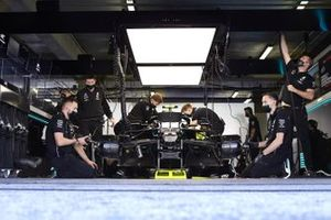 Mechanics work on the car of Valtteri Bottas, Mercedes F1 W11, in the garage