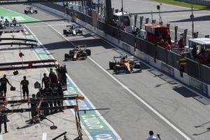 Lando Norris, McLaren MCL35, Max Verstappen, Red Bull Racing RB16, Pierre Gasly, AlphaTauri AT01, and Daniil Kvyat, AlphaTauri AT01, into the pits