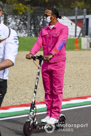 Lewis Hamilton, Mercedes-AMG F1, rides the track on an electric scooter
